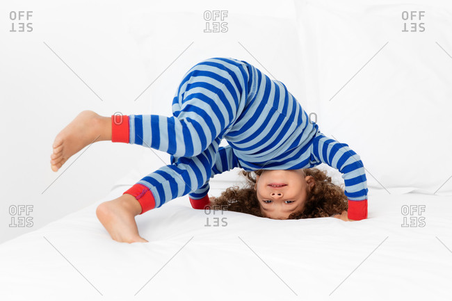 Funny toddler boy playing on white bed