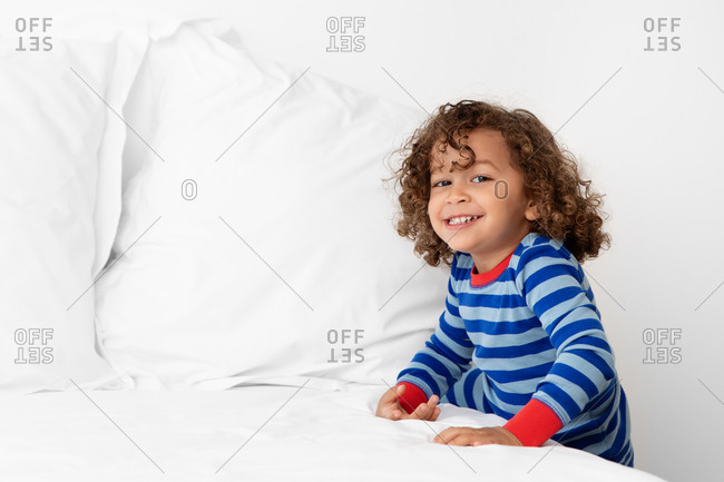 Portrait of cheeky young boy leaning on white bed