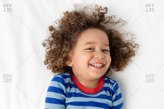 Portrait of happy young boy with curly hair
