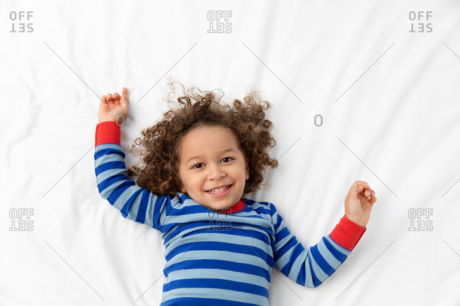 Portrait of happy toddler with curly hair lying on white bed