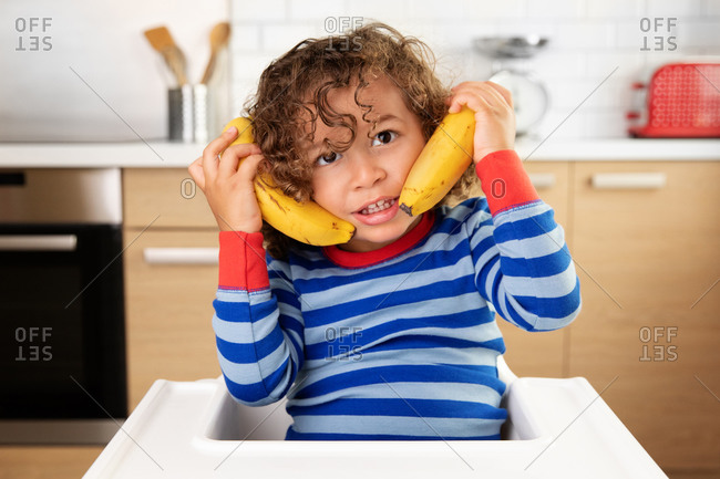 Funny toddler in high chair pretending to make a phone call with bananas