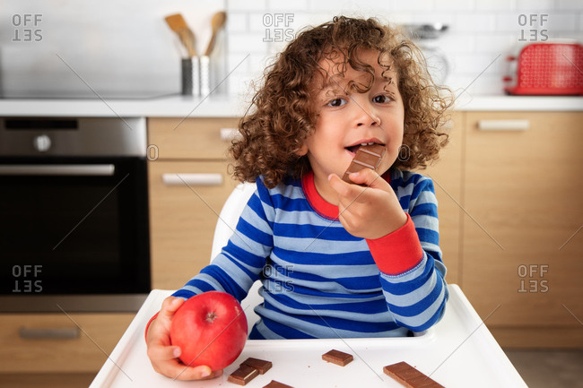 Cute toddler with curly hair eating snack in high chair