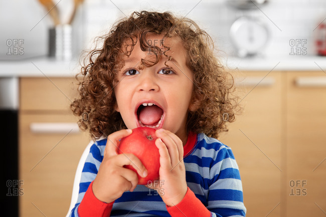 Cute toddler with curly hair eating a red apple