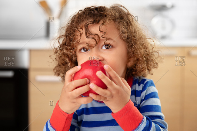 Young child with curly hair eating a red apple