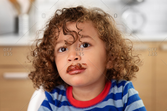 Portrait of cute toddler with curly hair and chocolate mustache