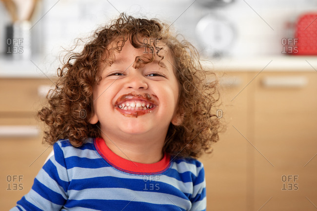 Portrait of laughing toddler with curly hair and chocolate mustache