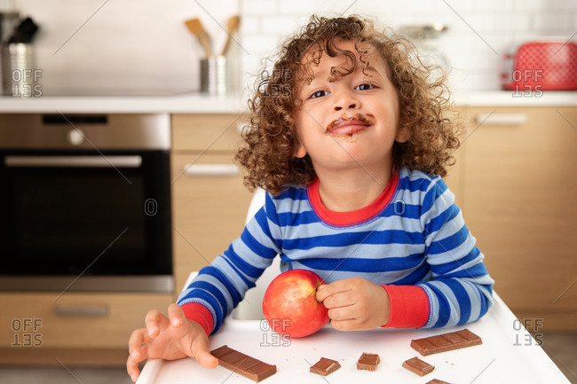 Smiling toddler with curly hair and chocolate mustache holding red apple