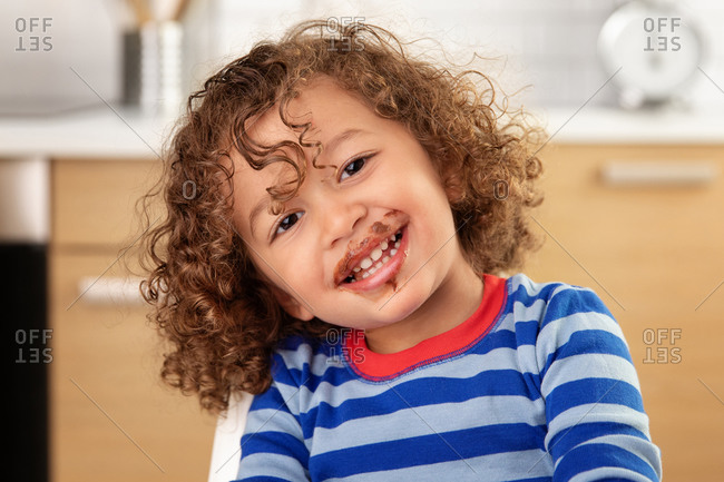 Portrait of smiling young child with curly hair and chocolate mustache