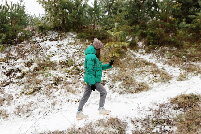 Young woman in green jacket looking at map on her phone while walking up snowy hill