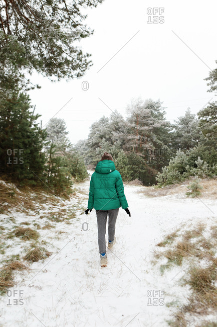 Young woman in green jacket walking through snow