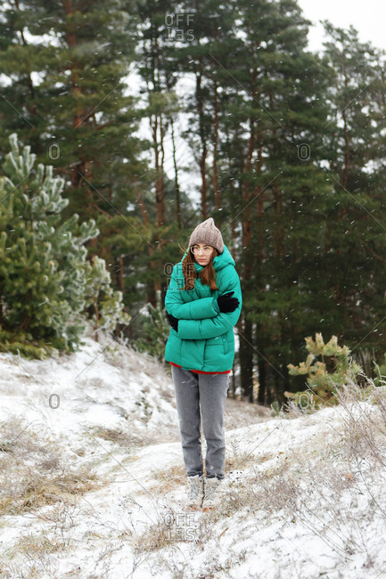Young woman in green jacket shivering outside on snowy day