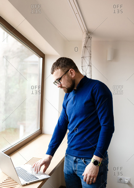 Young man with beard working on laptop by the window at home