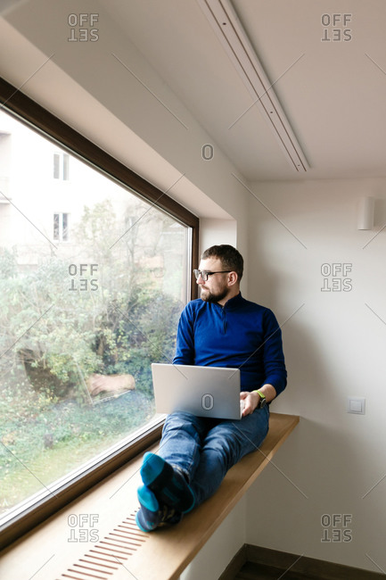 Young man with beard sitting on window ledge and working on laptop