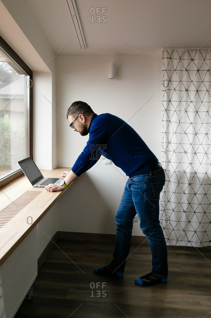 Young man with beard sitting on window ledge and working on laptop, close up