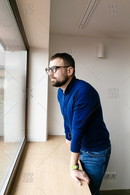 Young man with a beard in a blue jacket and jeans by the window at home