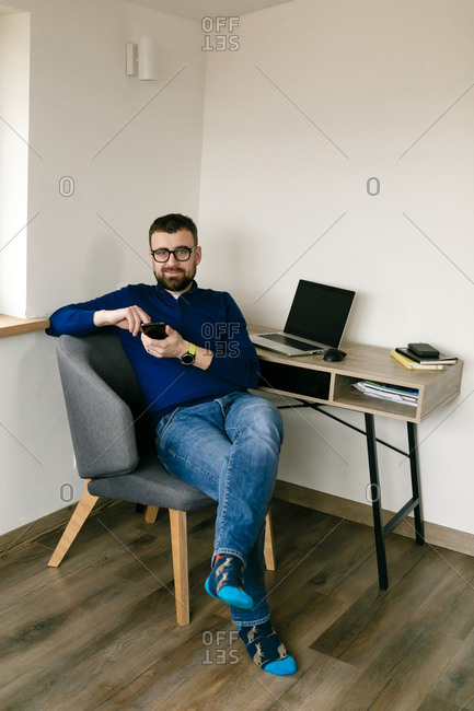 Young male businessman with a beard at his desk at home