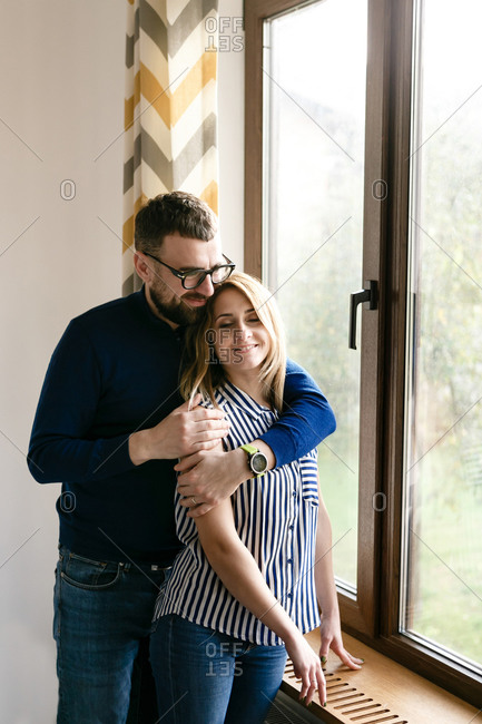 Young couple man with woman hugging standing by the window