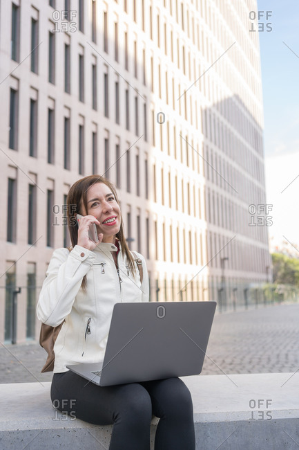 40-year-old business woman using a laptop at a city bank while talking on her cell phone