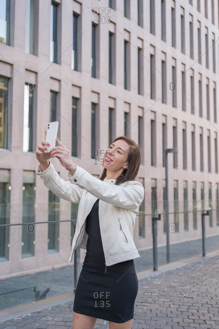 40-year-old business woman taking a self photo against office building