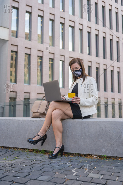 40-year-old woman with face mask holding credit card and using laptop computer.