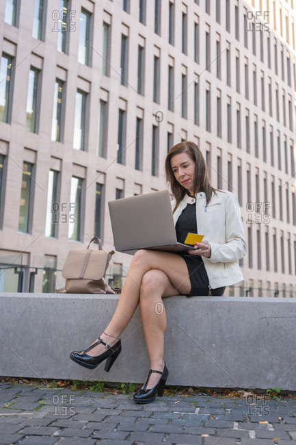 40-year-old woman holding credit card and using laptop computer.