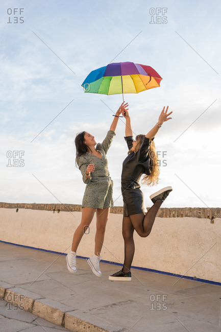 Two lovers women jumping with rainbow's umbrella against the sky in Sitges, Barcelona