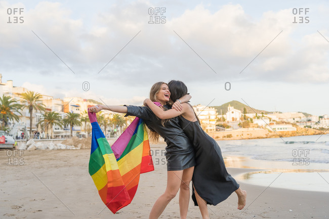 Lesbian couple in love on the beach with a rainbow flag, symbol of the LGBT community