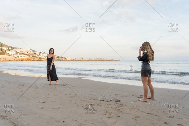 Two young women take photo of each other with camera in the Sitges's beach, Spain