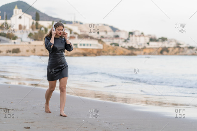 Pensive young woman wearing black dress walking along the seaside while listening to music on her headphones