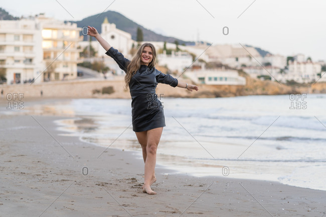 Young beautiful smiling blond woman in black dress happily standing with open arms with sea in background.