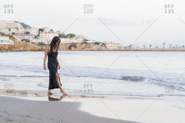 Pensive young woman wearing black dress walking along the seaside