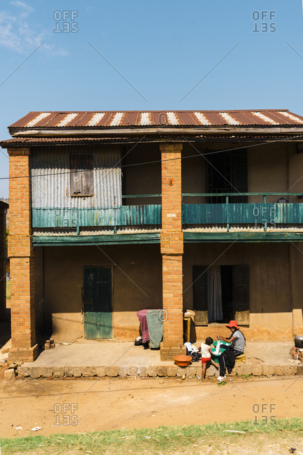 Antananarivo, Madagascar - October 12, 2019: Woman seated with child on porch of rural house made of bricks doing laundry
