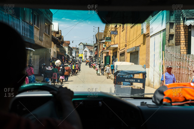 Fianarantsoa, Madagascar - October 12, 2019: View from inside a car of a crowded street with workers and vehicles in Fianarantsoa