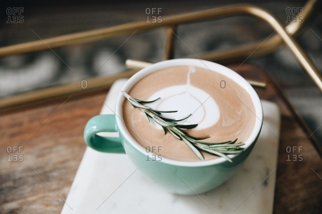 Close up of a cappuccino with a sprig of rosemary on a tray