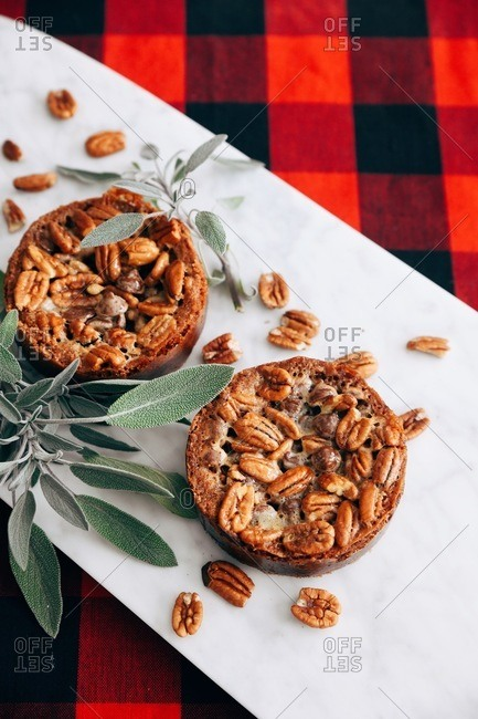 Overhead view of two pecan desserts on a plate with sage leaves