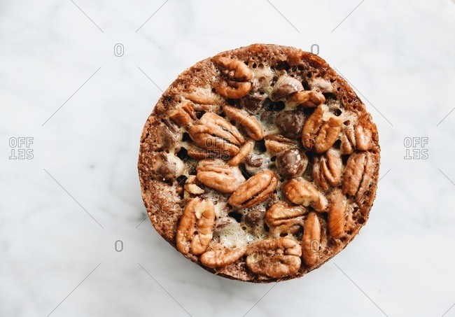 A round pecan dessert on white marble surface