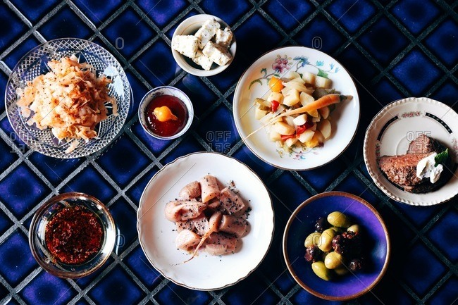 Overhead view of a delicious spread of food on blue tile