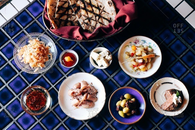 Overhead view of a delicious spread of food and a basket of pitas on blue tile