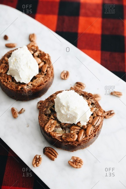Two pastries topped with whipped cream and pecans