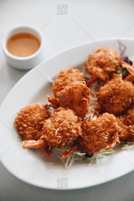 Close up of breaded shrimp served on an oval plate