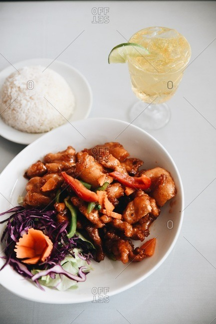 Gourmet Asian meat dish with rice on the side and served with a cocktail