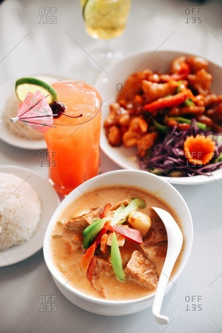 Asian soup with rice and meat dish on the side and served with a cocktail