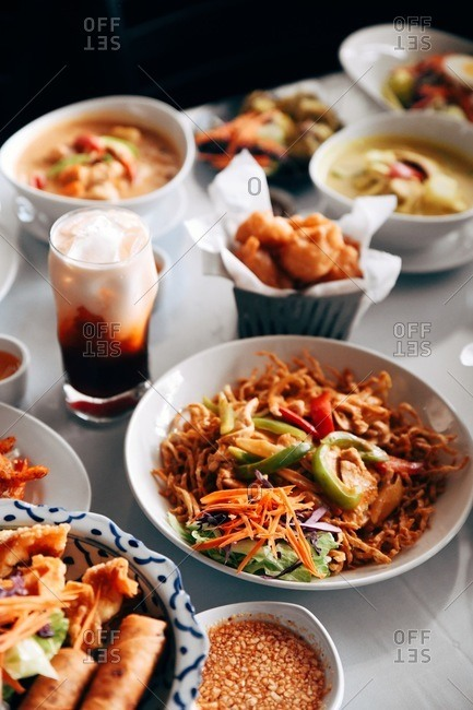 Variety of Asian dishes and cocktails served on white table