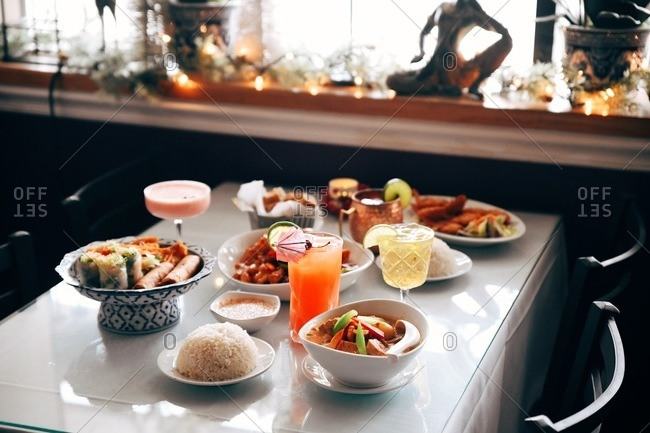 Table in an Asian restaurant with dishes and cocktails served on table
