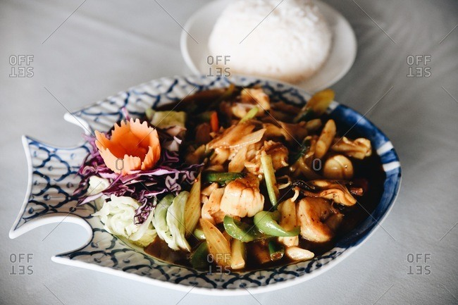 Gourmet Asian meat dish served in a fish shaped plate with rice on the side