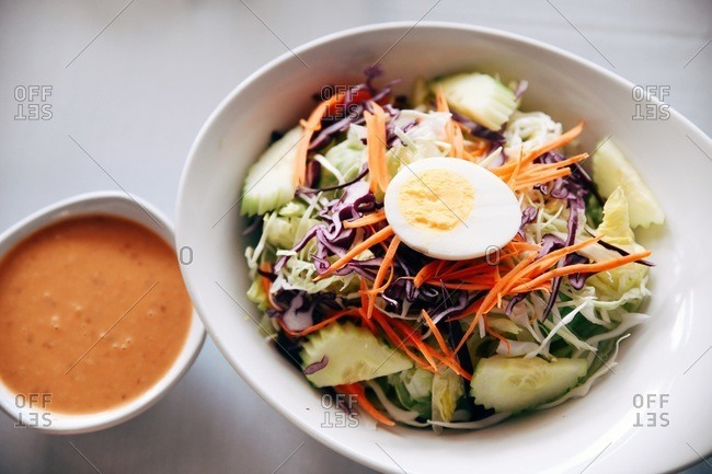 Healthy salad with hard boiled egg served in a bowl beside dressing