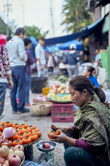 Luang Prabang, Laos - December 19, 2020: Side view of woman slicing and selling vegetable at her stall at the morning market