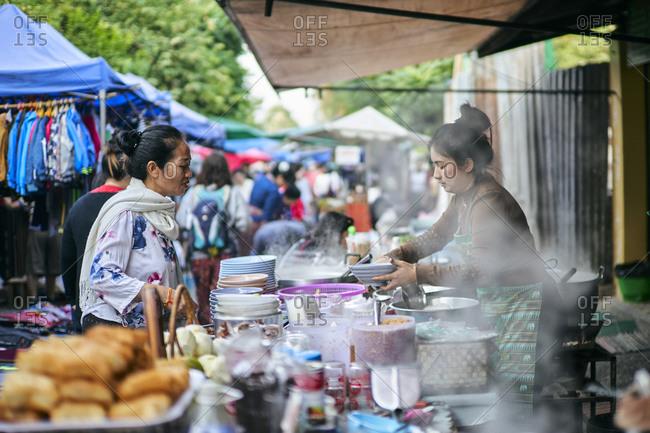 Luang Prabang, Laos - December 19, 2020: Woman selling food from stall at the morning market