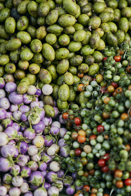 A colorful pile of small eggplants and other vegetables at a street market in Luang Prabang, Laos