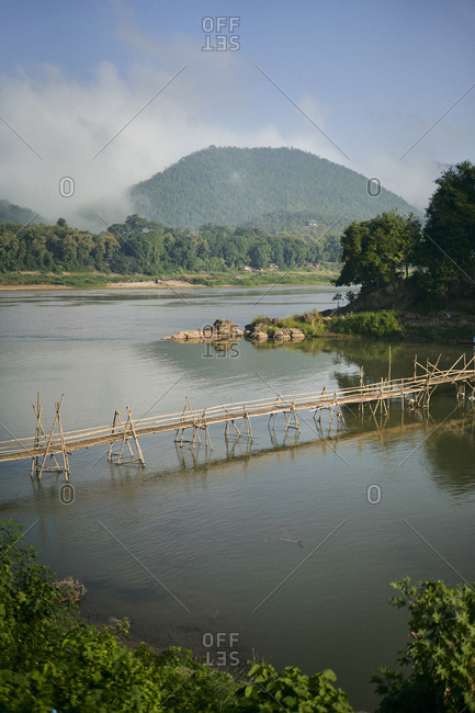 A bamboo foot bridge spans the Nam Khan river near its confluence with the Mekong in Luang Prabang, Laos